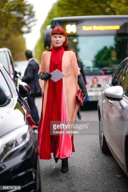 A guest wears a red and pink pleated dress has red hair outside Valentino during Paris Fashion Week Womenswear Spring/Summer 2018 on October 1 2017...