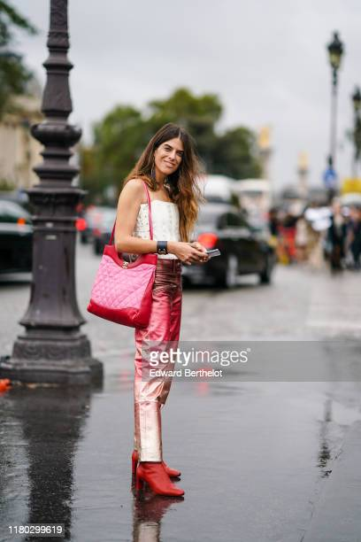 A guest wears a red and pink quilted Chanel 31 Shopping Bag a Chanel bracelet a white corset top shiny red and golden pants red heels shoes outside...