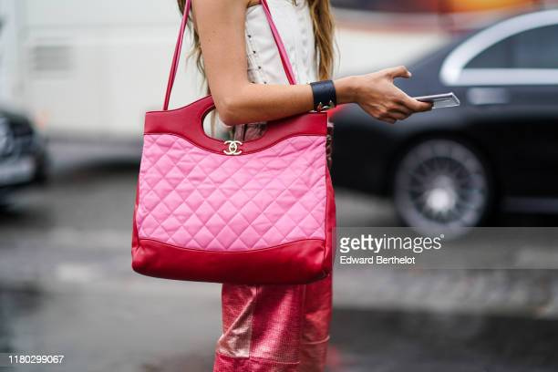 A guest wears a red and pink quilted Chanel 31 Shopping Bag outside Chanel during Paris Fashion Week Womenswear Spring Summer 2020 on October 01 2019...