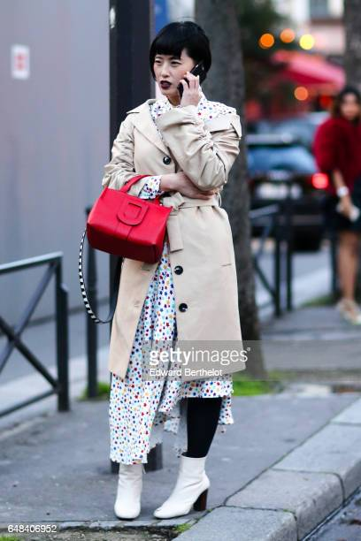 A guest wears a red bag a beige trench coat white boots and a multicolor star print dress outside the Galliano show during Paris Fashion Week...