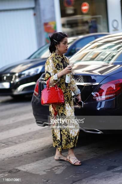 A guest wears a red bag a pleated yellow and black dress earrings shoes outside Valentino during Paris Fashion Week Haute Couture Fall/Winter...