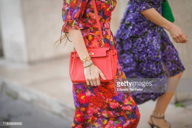 Guest wears a red bag, Dior bracelets, a colorful flower print dress with puff sleeves, during Paris Fashion Week -Haute Couture Fall/Winter...
