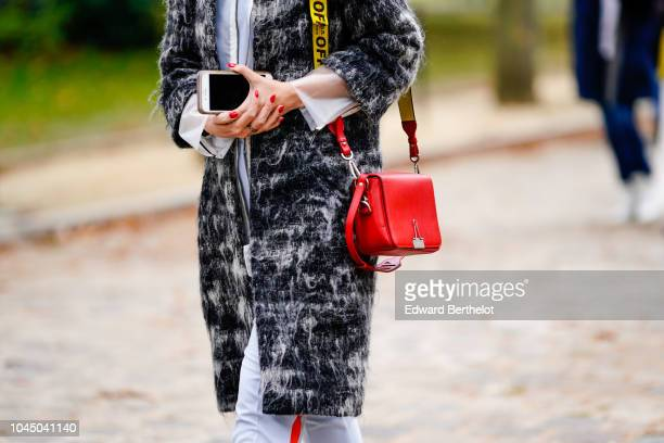 A guest wears a red bag outside Beautiful People during Paris Fashion Week Womenswear Spring/Summer 2019 on October 2 2018 in Paris France