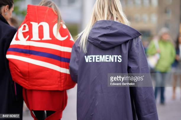 A guest wears a red Balenciaga oversized puffer coat a guest wears a Vetements rain coat outside Versus during London Fashion Week September 2017 on...