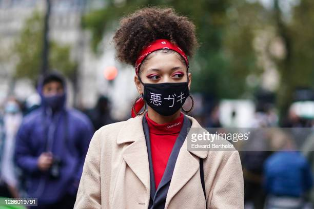 Guest wears a red bandanna, a black face mask with printed asian characters, a beige long trench coat, a red top, outside Yohji Yamamoto, during...