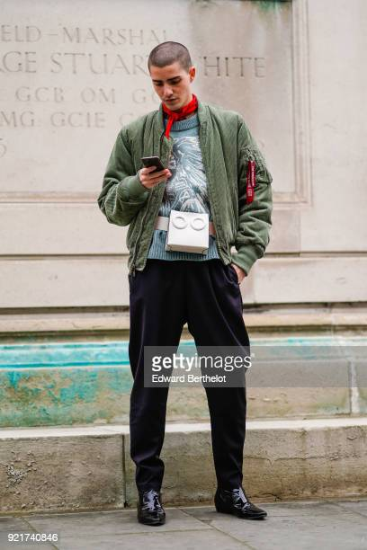 A guest wears a red bandanna a green bomber jacket a white bag during London Fashion Week February 2018 on February 18 2018 in London England