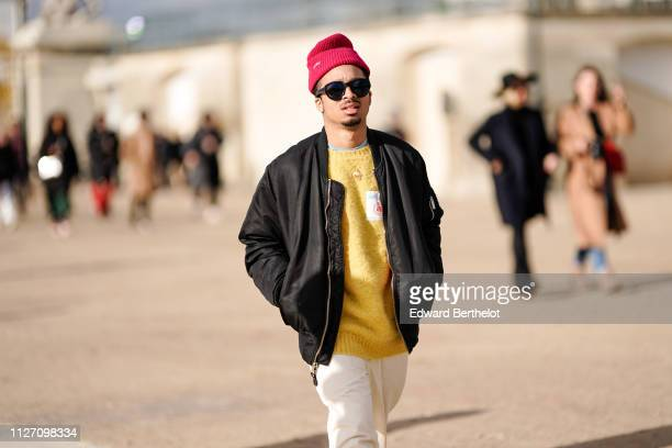 A guest wears a red beanie hat with the inscription Noah a yellow sweater a black bomber jacket white pants outside Louis Vuitton during Paris...