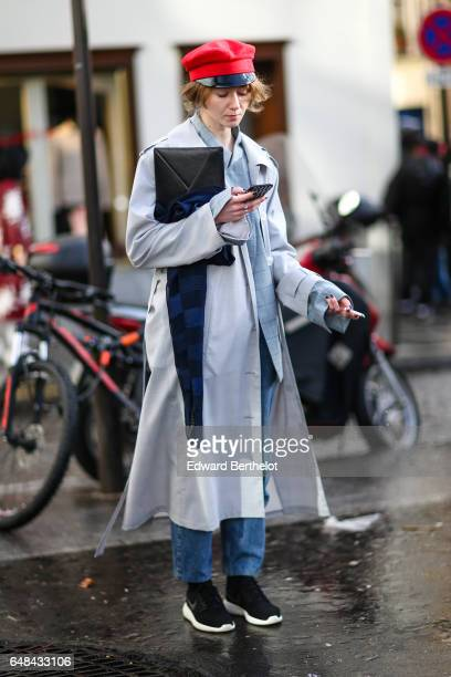 A guest wears a red beret hat a balck clutch and a gray coat outside the Valentino show during Paris Fashion Week Womenswear Fall/Winter 2017/2018 on...