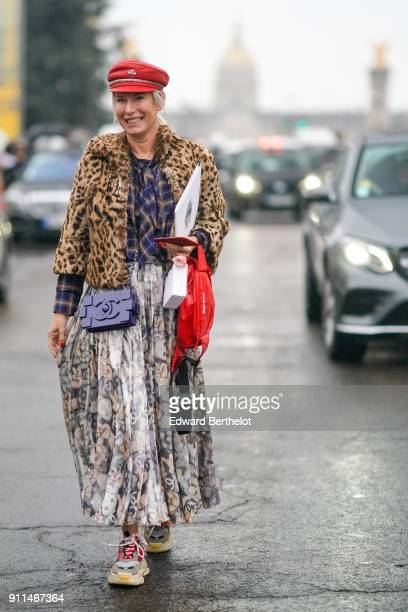 A guest wears a red beret hat a leopard print jacket a checked shirt a Chanel rectangular bag a flower print pleated skirt sneakers a red leather bag...