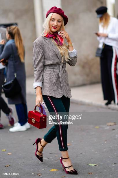 A guest wears a red beret hat a red bag a blazer jacket pants heels outside Valentin Yudashkin during Paris Fashion Week Womenswear Spring/Summer...