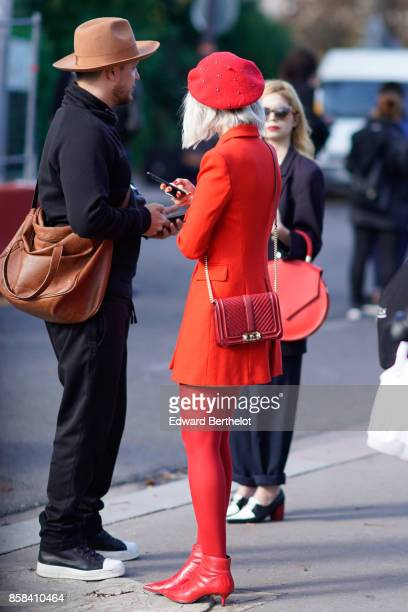 A guest wears a red beret hat a red jacket a red bag red tights red shoes outside Chanel during Paris Fashion Week Womenswear Spring/Summer 2018 on...
