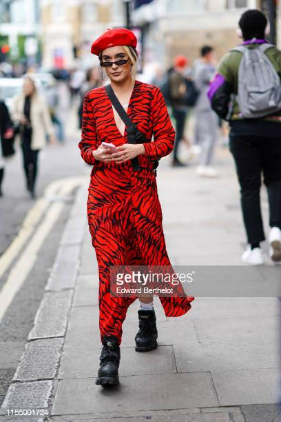 Guest wears a red beret hat, a red zebra print dress, black boots, sunglasses, a fanny pack bag, during London Fashion Week Men's June 2019 on June...