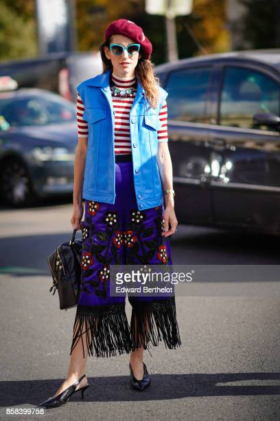 A guest wears a red beret hat green sunglasses a blue sleeveless jacket a striped tshirt a flower embroidered purple skirt with black lace shoes...