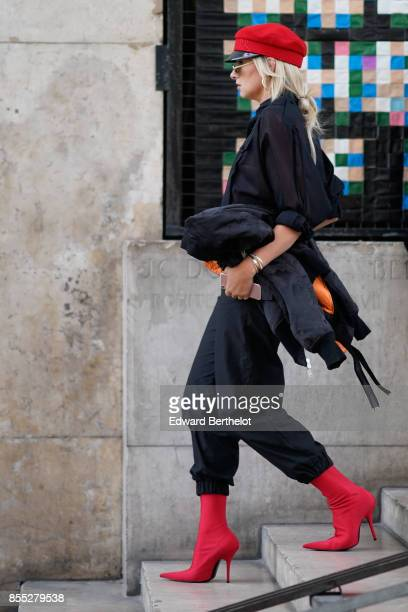 A guest wears a red beret hat red heels boots outside the Lemaire show during Paris Fashion Week Womenswear Spring/Summer 2018 on September 27 2017...