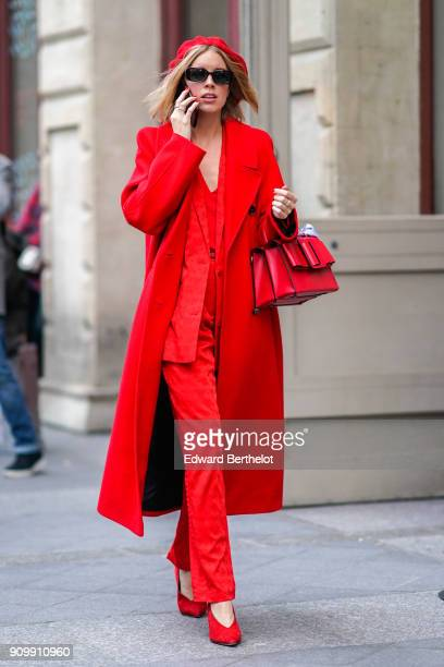 A guest wears a red beret hat sunglsses a red coat red pants red shoes a red bag outside Viktor Rolf during Paris Fashion Week Haute Couture...