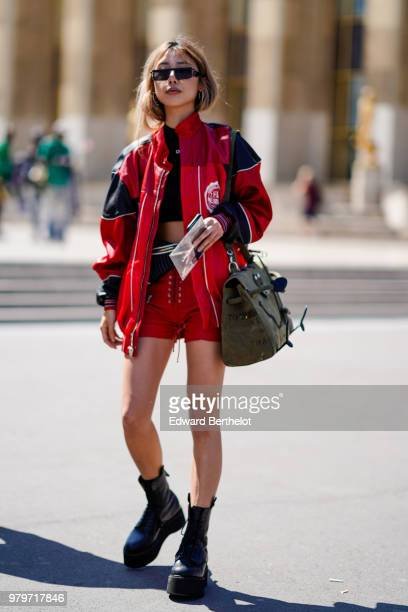 A guest wears a red bomber jacket a bag red shorts a Miu MIu bag sunglasses black shoes outside OffWhite during Paris Fashion Week Menswear...