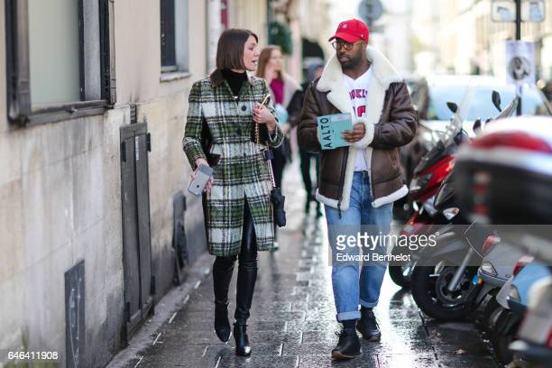 A guest wears a red cap glasses a brown aviator coat with white fur inner lining a white top blue denim jeans pants and black shoes outside the AALTO...