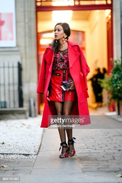 A guest wears a red coat a floral print top a red dress outside Kaviar Gauche during Paris Fashion Week Womenswear Spring/Summer 2018 on September 29...
