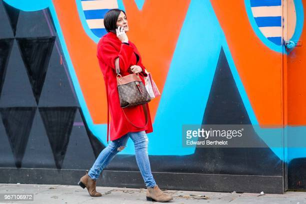 A guest wears a red coat a Vuitton brown bag blue jeans brown suede boots during London Fashion Week Men's January 2018 at on January 6 2018 in...