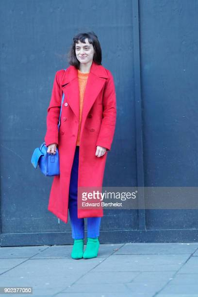A guest wears a red coat blue pants green shoes a blue bag during London Fashion Week Men's January 2018 at on January 7 2018 in London England