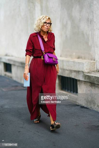 Guest wears a red coral necklace, a cyclamen-color Fendi bag, a burgundy front split long shirt dress, a black belt with a gold-tone buckle, black...
