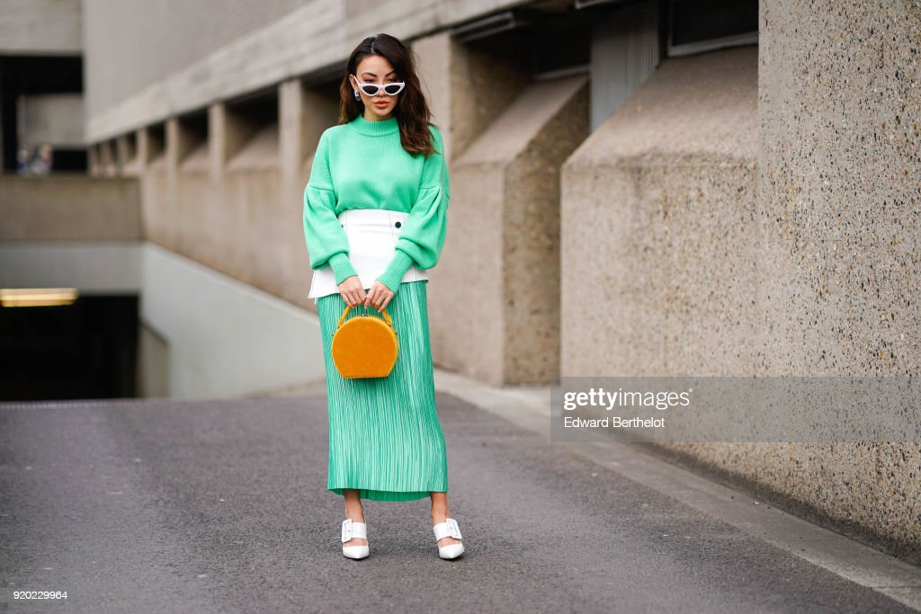 A guest wears a red dress, a yellow circular bag, white shoes, sunglasses, during London Fashion Week February 2018 on February 18, 2018 in London, England.