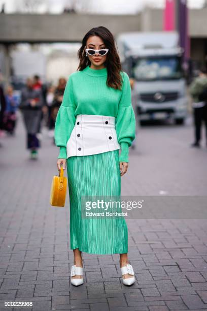 Guest wears a red dress, a yellow circular bag, white shoes, sunglasses, during London Fashion Week February 2018 on February 18, 2018 in London,...