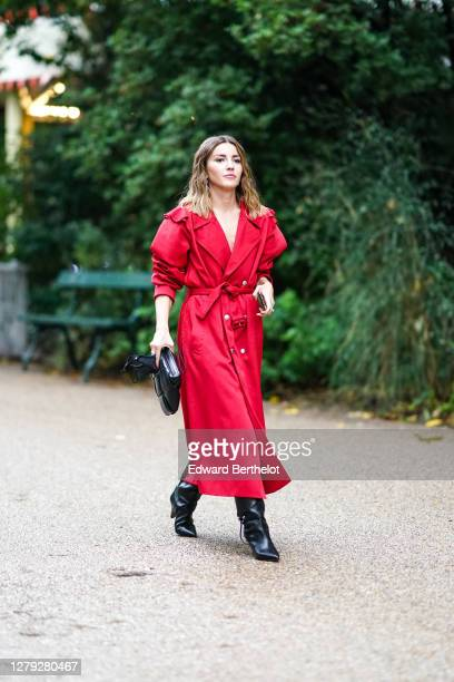 Guest wears a red dress / long trench coat, black pointy leather boots, a black leather bag, outside Koche, during Paris Fashion Week - Womenswear...