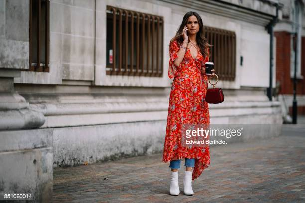 A guest wears a red dress with floral prints outside Preen by Thornton Bregazzi during London Fashion Week September 2017 on September 17 2017 in...