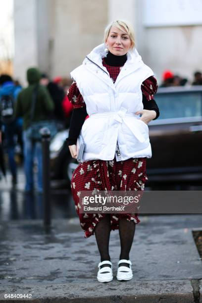 A guest wears a red dress with flower print white shoes and a white sleeveless puffer jacket outside the Mashama show during Paris Fashion Week...