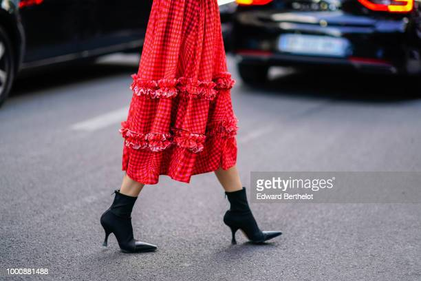 A guest wears a red dress with ruffles and black heels boots during Paris Fashion Week Menswear SpringSummer 2019 on June 22 2018 in Paris France