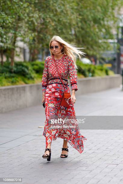 Guest wears a red floral print dress, a red bag with metallic ring, black shoes, during London Fashion Week September 2018 on September 16, 2018 in...
