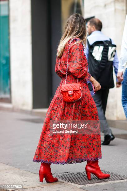 Guest wears a red floral print dress, a red Chanel quilted bag, red boots, outside the Peter Pilotto show during Milan Fashion Week Spring/Summer...