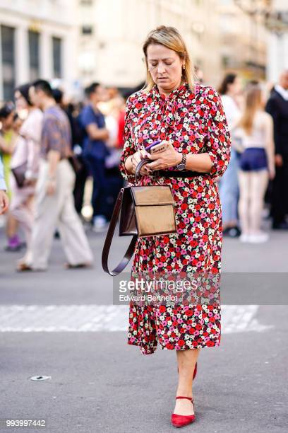 A guest wears a red floral print dress and red shoes a bag outside Fendi during Paris Fashion Week Haute Couture Fall Winter 2018/2019 on July 4 2018...