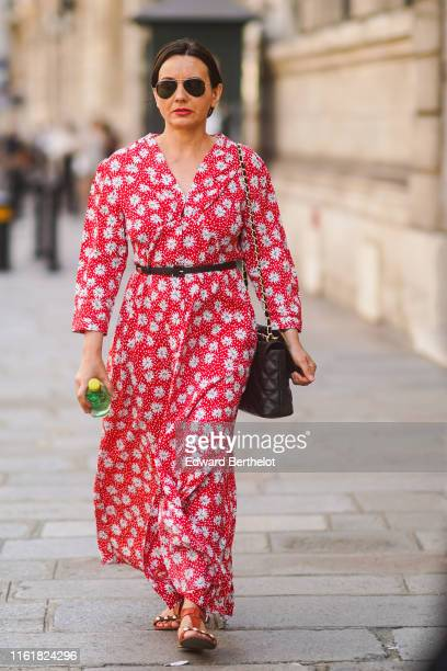 Guest wears a red floral print dress, outside Ralph & Russo, during Paris Fashion Week -Haute Couture Fall/Winter 2019/2020, on July 01, 2019 in...