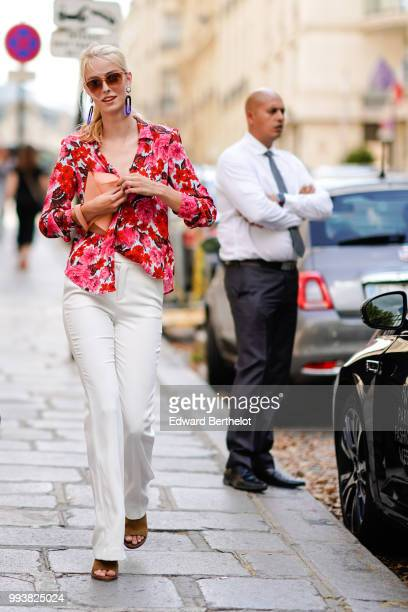 A guest wears a red floral print shirt white flared pants brown shoes sunglasses purple long earrings during Paris Fashion Week Haute Couture Fall...