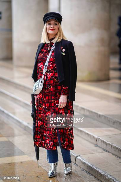 A guest wears a red flower print dress an black and white striped OffWhite shoulder strap bag a jacket silver shiny shoes a black beret hat during...