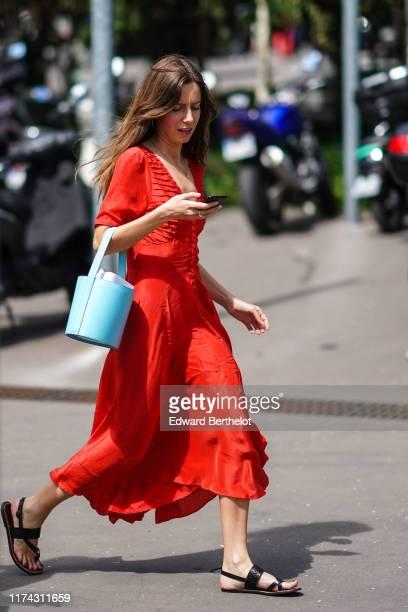 Guest wears a red flowing dress, a light blue bucket bag, black flat sandals, outside Acne Studios, during Paris Fashion Week - Menswear...