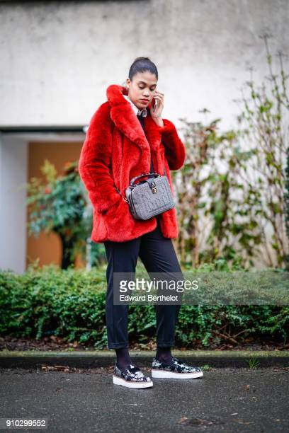 A guest wears a red fur coat a purple bag black cropped pants sneakers outside Christophe Josse during Paris Fashion Week Haute Couture Spring/Summer...