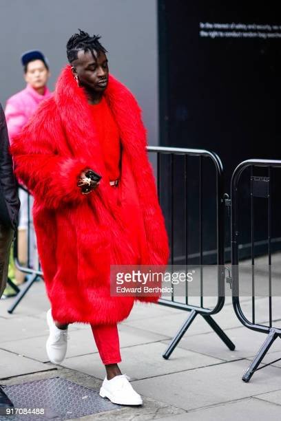 A guest wears a red fur coat white sneakers during London Fashion Week Men's January 2018 at on January 6 2018 in London England