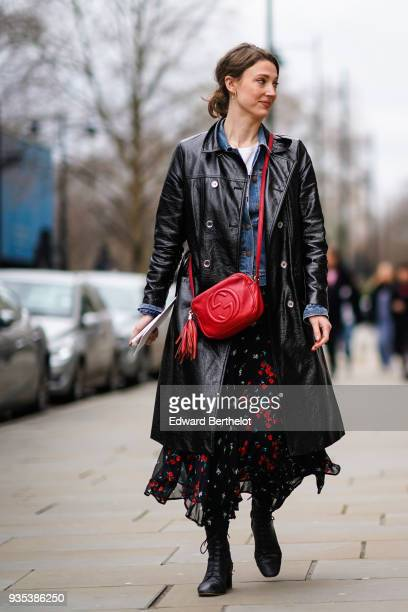A guest wears a red Gucci bag a black leather coat a mesh black lace flower print skirt during London Fashion Week February 2018 on February 18 2018...