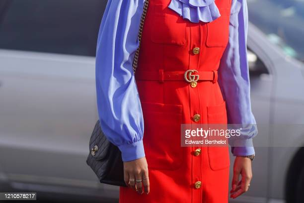 Guest wears a red Gucci belt, purple ruffled shirt, a red dress with golden buttons, outside Chanel, during Paris Fashion Week - Womenswear...