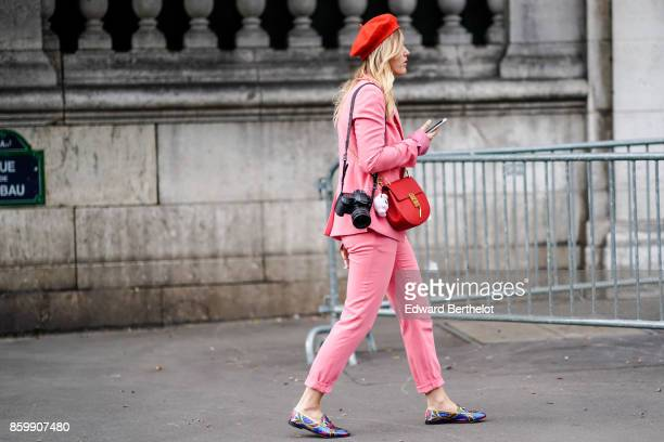 A guest wears a red hat a pink pantsuit with turnedup hems pants a red bag multicolor shiny moccasins outside the Dries Van Noten show during Paris...