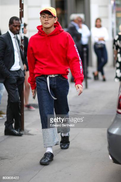 A guest wears a red hoodie a cap blue denim jeans pants black shoes white socks outside the Hermes show during Paris Fashion Week Menswear...