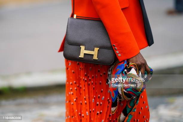 Guest wears a red jacket, a red pleated flowing dress with blue and brown designs, a black Hermes bag, and holds a colorful scarf, outside Hermes,...