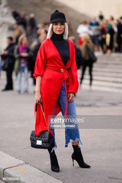 A guest wears a red jacket cropped ripped jeans a bag a cap outside Hermes during Paris Fashion Week Womenswear Spring/Summer 2018 on October 2 2017...