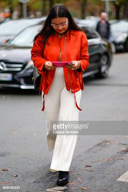 A guest wears a red jacketwhite flare pants and black platform patent shoes outside Manish Arora during Paris Fashion Week Womenswear Spring/Summer...