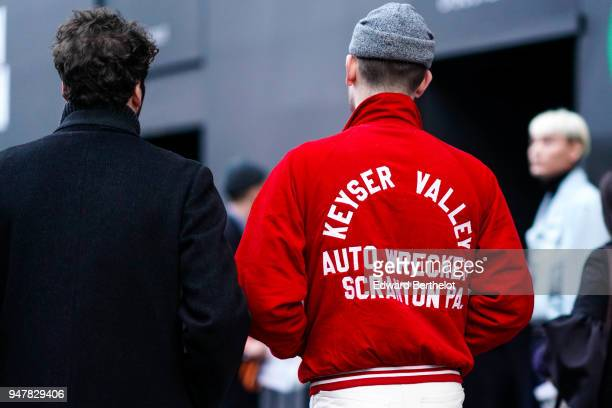 A guest wears a red 'Keyser Valley' jacket a gray beanie hat during London Fashion Week Men's January 2018 at on January 6 2018 in London England