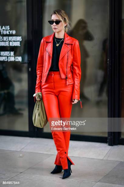 A guest wears a red leather jacket outside the Lemaire show during Paris Fashion Week Womenswear Spring/Summer 2018 on September 27 2017 in Paris...
