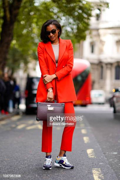 A guest wears a red long blazer jacket cropped suit pants a rectangular rigid case bag Chanel sneakers shoes during London Fashion Week September...